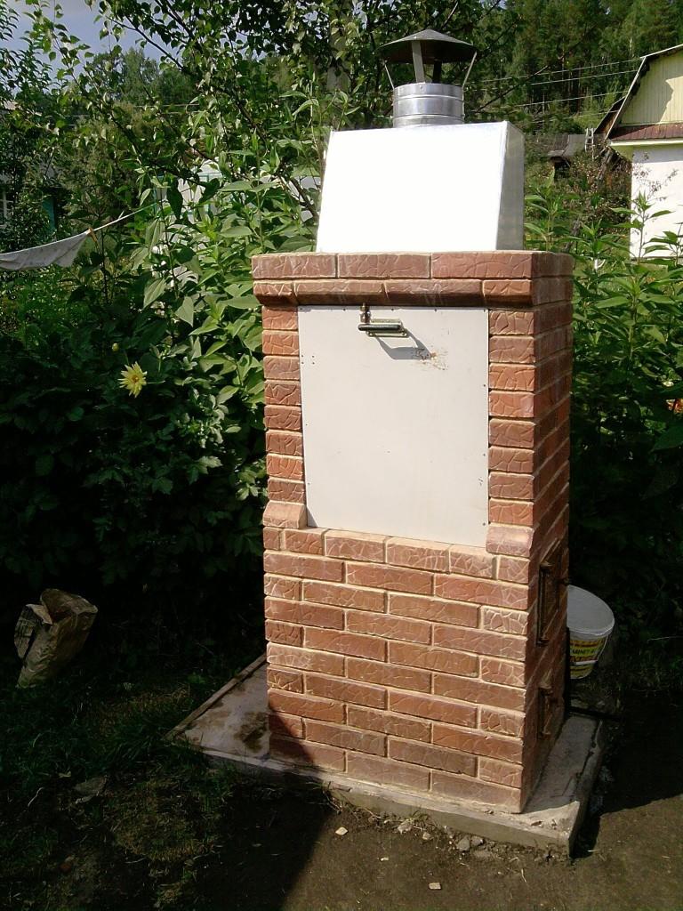 Коптильня из кирпича, установленная во дворе дома